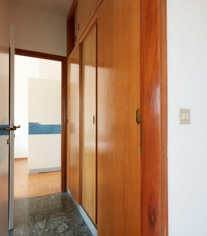 Corridor with wooden wardrobe and open door, interior in country house
